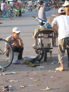 A flat tyre doesn't need to be a problem, guys who come and fix them appear out of nowhere. Mobile motorbike repair repair shop - client sits and waits while his tube gets fixed, Hanoi, Vietnam.