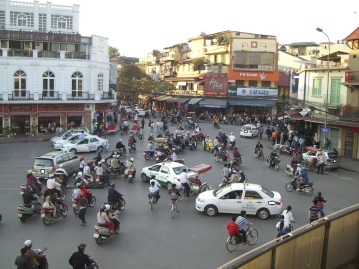 On a quiet time for traffic, looking down from Highlands Coffee situated in a 5 story building on the corner of Dinh Tien Hoang and Cau Go Streets, this is looking down Hang Gai Street, Hanoi. Good place to sit up in this building and watch traffic at night.