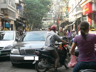 More cars more traffic jams - this car driver forgets he's driving a car now, Hanoi, Vietnam.