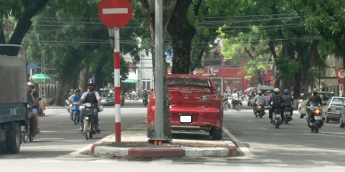 2010 photo - Good use of not used space parking - this person uses the middle barrier between 2 roads leading up to an intersection, looks a bit funny seeing some random car parked there, but safe enough and quite a good idea, Hanoi, Vietnam.