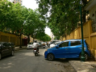 2010 photo - Angle footpath parking - this is actually a good solution to limited parking space, use one side of the street for parking but get the driver to back in and up onto the footpath on an angle with the assistance of a attendant who collects the parking fee. Heaps of cars can fit into a limited space this way on a Hanoi Street, Vietnam.