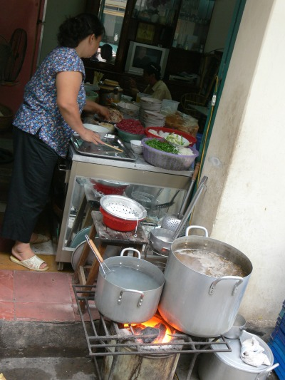 Vietnamese lady is cooking with charcoal in her well organised kitchen in Hanoi, got the stock cooking and all condiments lined up.