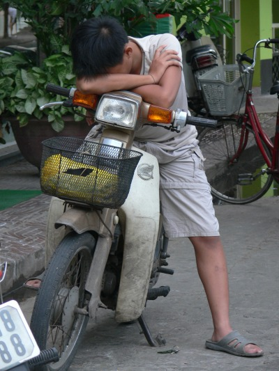 Standing up on your motorbike + sleeping - You've got to be seriously tired to try this one at home.