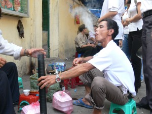 Vietnamese water pipe is lit then shared around.
