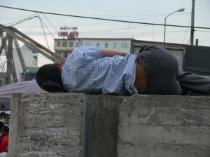 3. Sleeping man uses his shoes for a pillow, he is sound asleep.