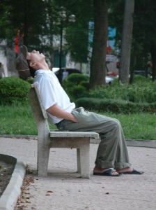 Vietnamese man snores as he sleeps on a park bench.