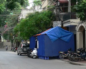 In Hanoi where space is limited a tent is is erected to house the wake. A sign on the door way lets people know who has passed away. The new tent put up easily tells all the neighbors there has been a death in the family. The funeral tent accommodates the people who will come to visit for 2 to 5 days. If it is a young person this part will be done very quickly.