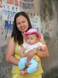 Mother and baby portrait has a lovely graffiti as a back drop.