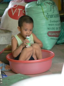 Rice vendor having a wee break - little Vietnamese boy sits in a rice bowl having a drink.
