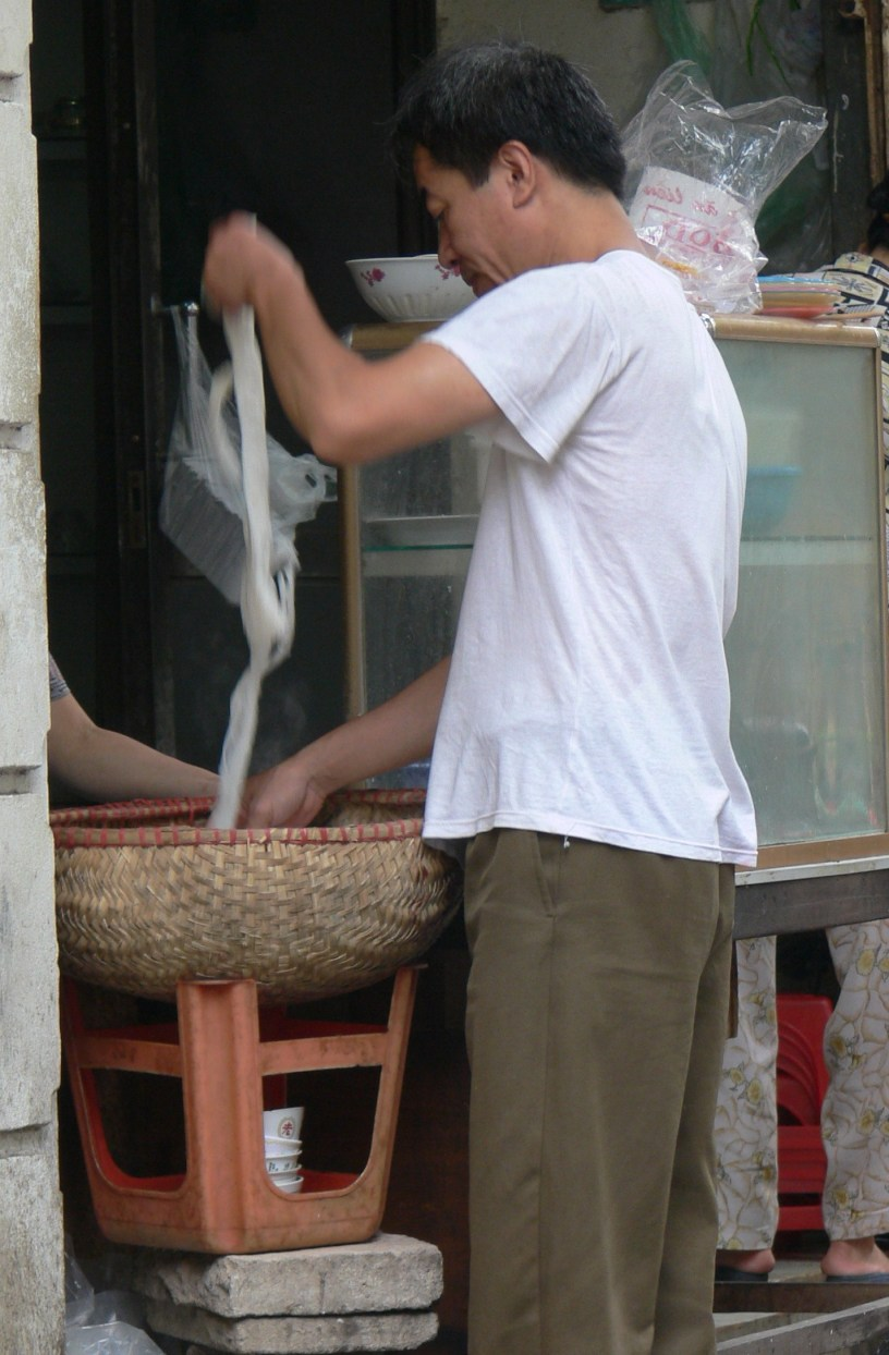 Noodle man !! Hand made noodles - taste the freshness - I like his use of a red plastic chair.