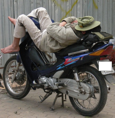 Vietnamese man sleeps soundly on a motorbike