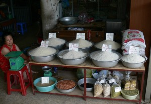 This lady sells rice, peanuts and beans by the kg.
