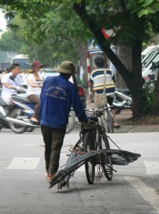 This delivery man and bike has a very heavy load of 15+ metal rods.