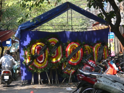 A funeral marque in Hanoi shows flowers delivered by other mourners who have left them as they came in. As people attend the funeral they leave their flowers, pray to the altar, leaving an envelope with money for the family. Then it is time to sit and talk with the mourners.