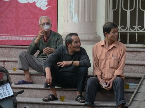 Vietnamese man enjoys a social cuppa and a smoke with friends in Hanoi