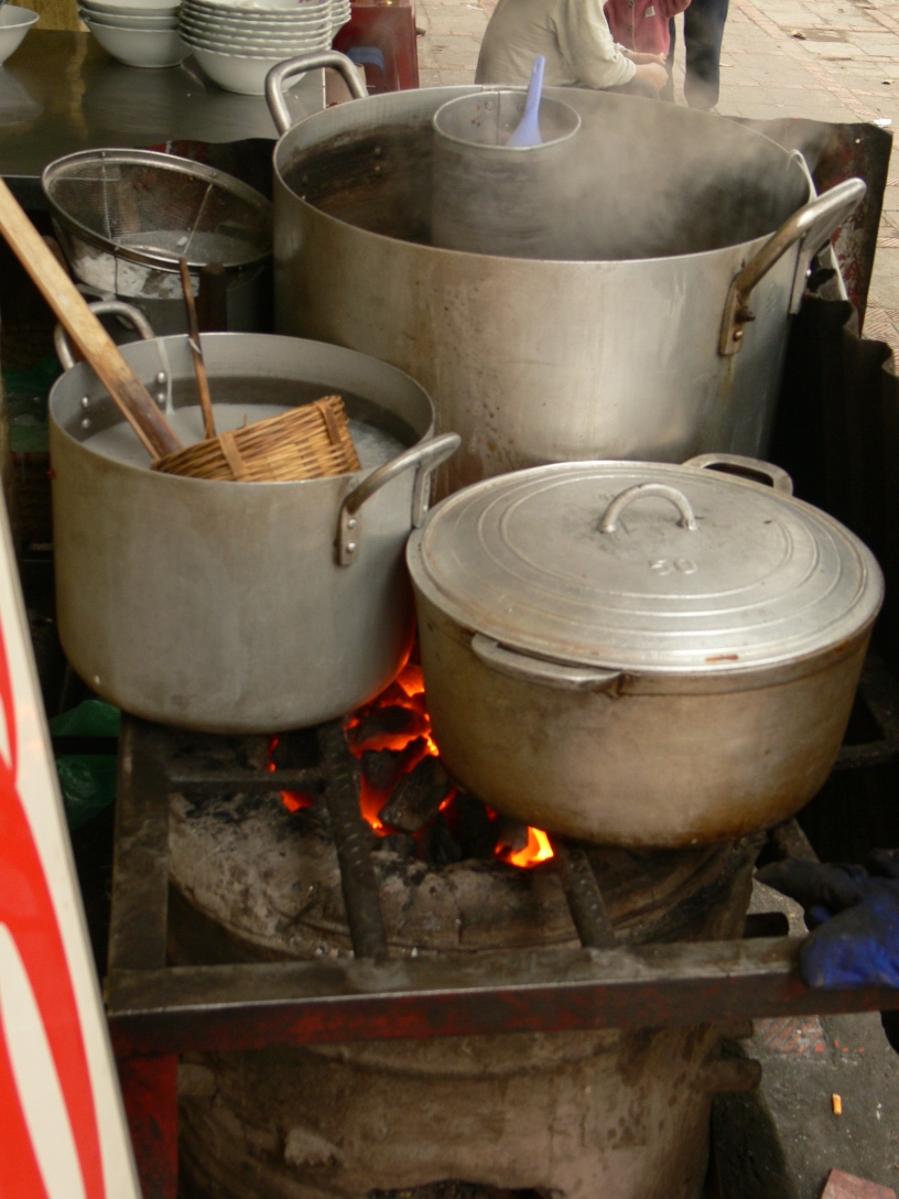 Large pots cooking over charcoal