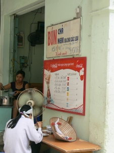 Street food shop, price 2010 state Bun Cha as D15,000 = 78 cents which would be pretty expensive if you only earned $2 a day.
