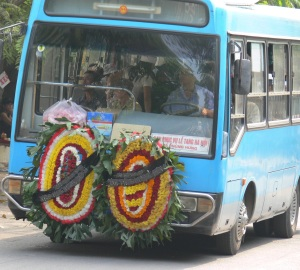 A bus containing mourners and coffin escorts the deceased person to the burial site.