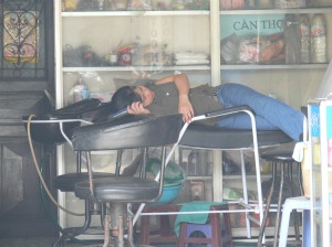 Vietnamese hairdresser sleeps on hair washing bench