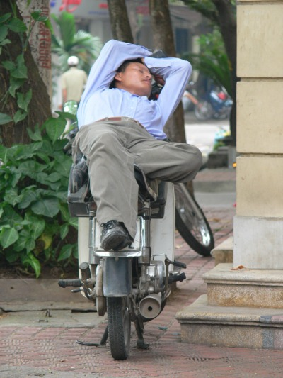 Vietnamese man sleeping on his motorbike - rolling over is not an option.