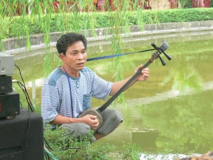 Musician at Ethnology Museum plays a 3 stringed lute for open air performance in small pond for its purpose.