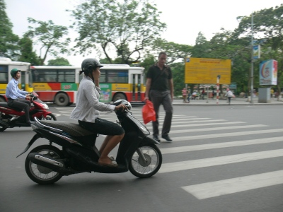 A foreigner is crossing on the pedestrian crossing but keeping a close eye on the lady driver who is on the phone.