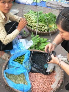 Street vendor from Hanoi looks at me, while selling tiny limes, dried beans, bananas and greens. A Vietnamese women goes through her wallet finding the correct money.