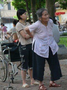 Vietnamese lady is wheeled to the park in her wheelchair where her does her exercises with a personal trainer or granddaughter who she is nearby,