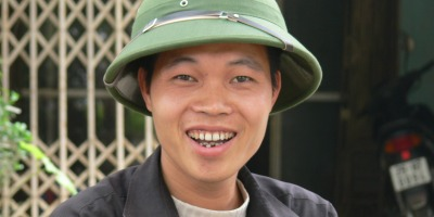 Vietnamese man in Hanoi wears a military hat for a helmet, he is a motorbike driver.