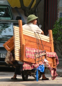 In Hanoi this Vietnamese man has a dismantled single bed with bed side table, just a touch lost !! Pre-helmet laws, Dec 2007.