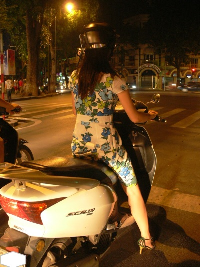 Well dressed Vietnamese woman on a motorbike in Hanoi.