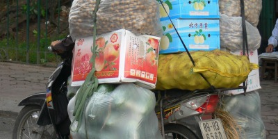 Exceptional packing job !! Fruit, water melons, peaches, melons, lychees and green mangoes on a motorbike in Hanoi, load so big you cannot see the rider.