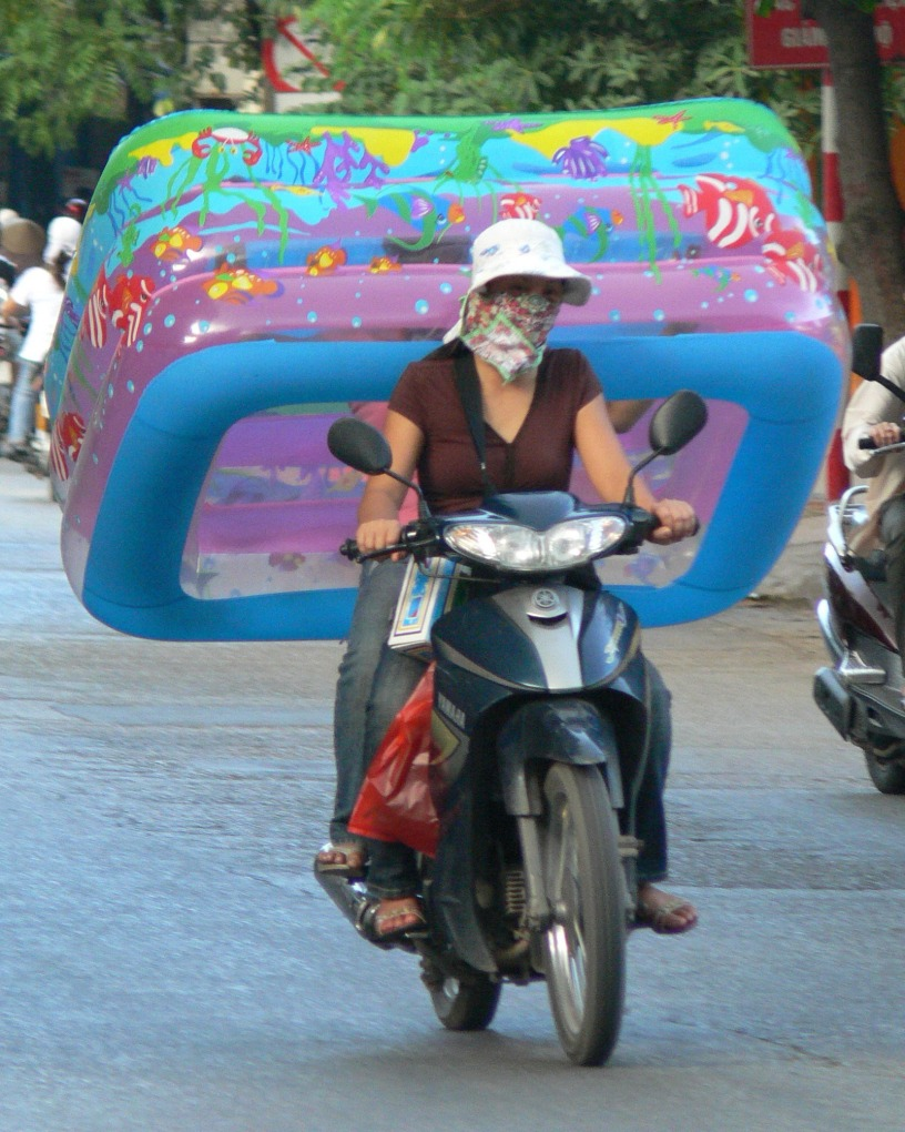 A lady rides a motor bike and on the back is someone holding a big blow up pool . . .the kids are going to love this, lucky little sis was with me, then she could hold it, otherwise I couldn't take it home blown up, now that would be a problem ! Pre helmet Law 2007.