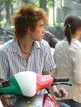 Young Vietnamese man sits on a bike while waiting for someone.