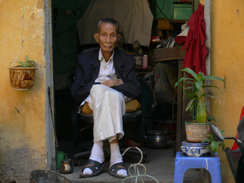 A Vietnamese elderly man sits in his doorway of his home watching the world go by.