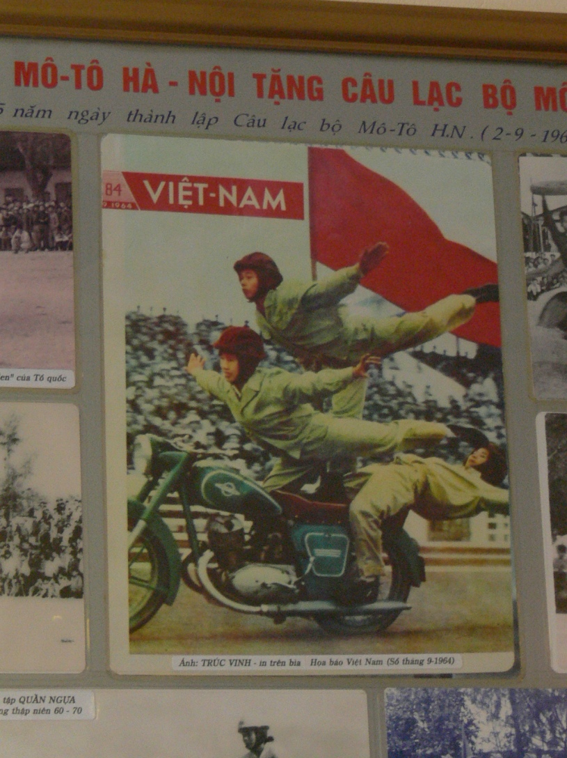 Ca Phe Xe Co on Hang Bun Street, near Trúc Bạch Lake celebrates motorbiking, don't try this at home !! 3 people riding a motorbike or should I say sitting, standing and doing acrobatics on the bike holding a red flag while it is driven.