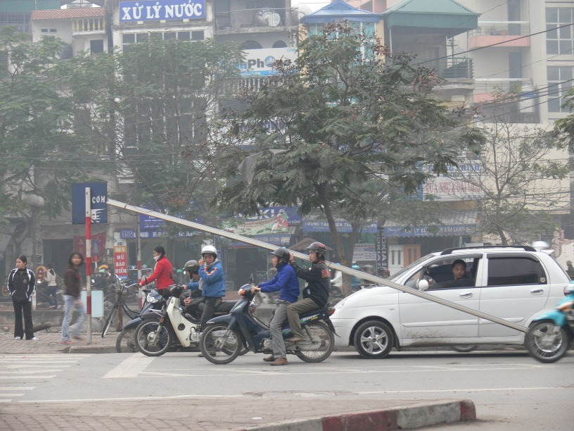 Two Vietnamese men on a motor bike, one holding a 5 - 6 meter length - slightly over length. Can't wait to see this guy go around a corner, I am sure everyone know to beware of him !