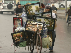 A Vietnamese man has his bicycle loaded up with a a beautiful load - 7 paintings, 2 large blue and white vases, big ginger jar, 2 small vases and what ever is on the back we can't see.