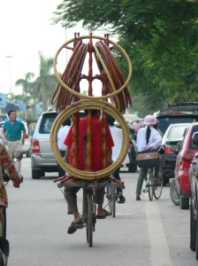 Vietnamese man rides his bicycle with multiple hoops on a stand - Your guess is as good as mine to what these are, other than hoola hoops??