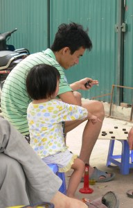 A small child sits beside a Vietnamese man who is playing a board game - If you move that one next, then it will open up for the other one. Why doesn't listen to me is what I want to know.