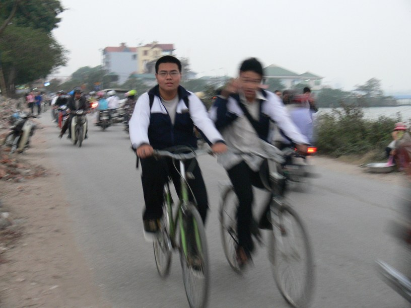 Vietnamese students on way home on bicycles, on Lac Long Quan Street while road while road was getting developed.