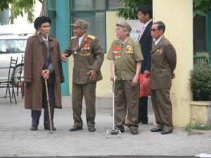 Heavily decorated Vietnamese gentlemen meet up for a function.