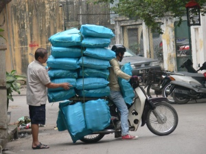 A motorbike in Hanoi has 18 blue bags of goods on his motorbike, as the drive sits right on the edge of the seat - I reckon we fit another on the top !!Crazy Load