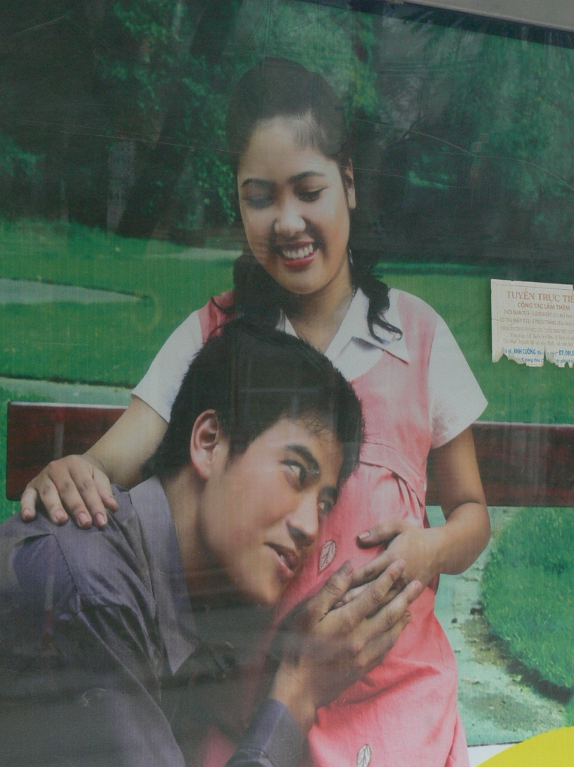 Advertising board, Vietnamese man with head to wife's tummy who is pregnant.
