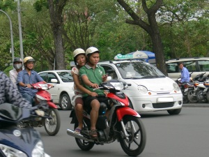 A Vietnamese man with a woman on the back of his motor bike is texting/messaging while while driving . . . watch out for these guys when crossing the road.
