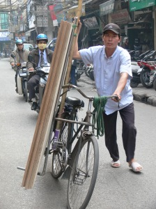 Vietnamese man has 5 large sheets of lining material on his bicycle that he is pushing, can you imagine how heavy this is? Actually they weigh about 50-70 lbs each or 20-30 kgs each = 250 - 350 lbs or 100-150 kgs !!