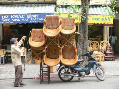 Vietnamese Man has 9 cane chairs with arms on, on his motorbike . Great packing / balancing skills, he got all of the 9 cane chairs on as expected and perfectly balanced ready for delivery - impressive and where do you start ?