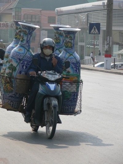 A Vietnamese man rides a motor bike - You have just got to love this guy, he has 4 massive, expensive looking vases as his load, but still gives me the thumbs up !!