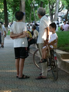1. A Vietnamese granddad is talking to his friend for ages while a little grandson sits on back of his bike.