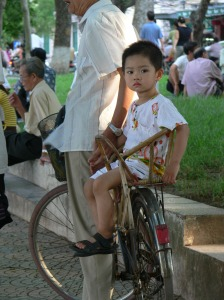 Little Vietnamese boy sits patiently waiting on the back of a motorbike while his grandfather but doesn't mind as . .. . .
